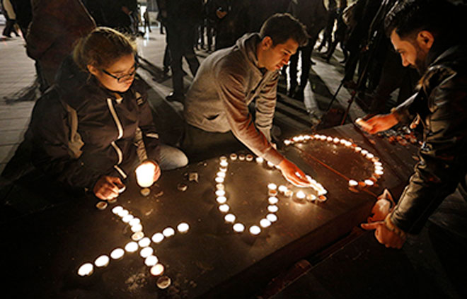 Murder in Paris: People light candles in the shape of a cross and heart in Republique square in Paris on November 14 in memory of victims of terrorist attacks. Co-ordinated attacks the previous evening claimed the lives of 129 people. The Islamic State claimed responsibility. Photo: CNS