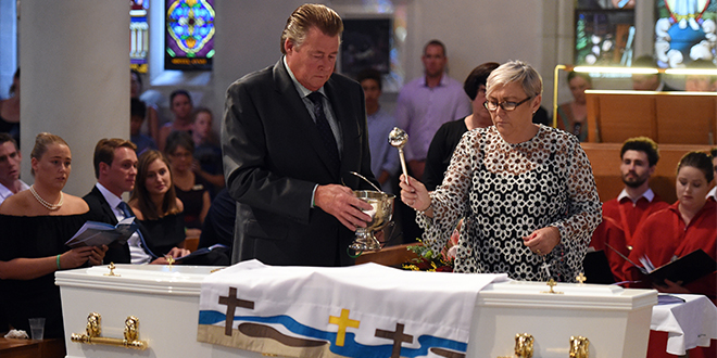 Tearful goodbye: Steven and Mary-Leigh sprinkle the coffin of their son, 18 year-old one-punch victim Cole Miller during his funeral service in Brisbane, Wednesday, Jan. 13, 2016. Cole died in hospital on January 4 from massive brain trauma a day after allegedly being hit in Brisbane's Fortitude Valley. Photo: AAP Image