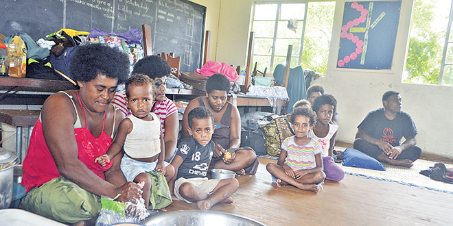 Monster storm: Families from Wainiveidilo settlement prepare their lunch at a school used as an evacuation centre in Navua, Fiji, after Cyclone Winston ripped through the country.