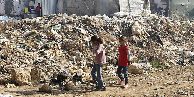 Syrian girls walking near rubbish