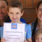 Isabella Mackay holding her World's Greatest Shave Certificate