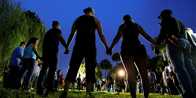 Overcoming hatred: People hold hands in a circle during a June 12 vigil in an Orlando, Florida, park following a mass shooting at a night club in the city earlier that morning. Photo: CNS
