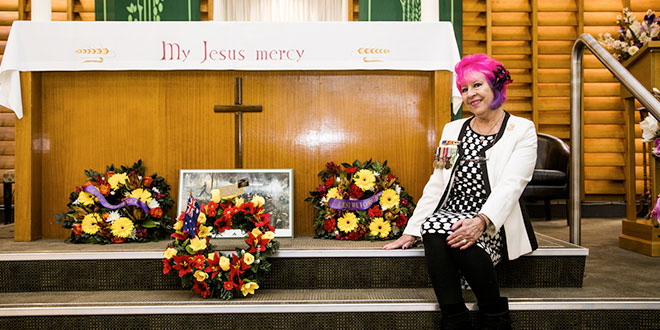 Remembering Douglas: Frankie O'Leary sitting on the steps at the altar with wreaths after the memorial Mass at St Fabian's Church, Yeerongpilly.