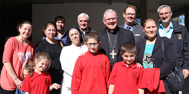 New home: Archbishop Mark Cole-ridge, parish priest Fr Dan Carroll and Darra's Our Lady of the Sacred Heart Primary School principal John O'Connor welcome newly-arrived Iraqi refugee families. Photo: Mark Bowling