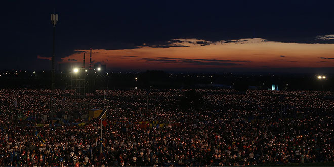 Sea of faith: World Youth Day pilgrims hold candles during eucharistic adoration with Pope Francis at the July 30 prayer vigil at the Field of Mercy in Krakow, Poland.                          Photos: Emilie Ng