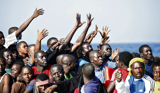 Differing approaches: Migrants reach out from a boat during rescue operations in the Mediterranean Sea. 								 Photo: CNS