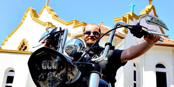 Biker priest: Fr Andrzej Kolaczkowski on his bike in front of Our Lady of Victories Church, Bowen Hills.  Photos: Mark Bowling