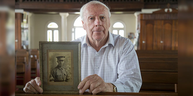 Noel Synnott holding a photo of his uncle who served in the First World War
