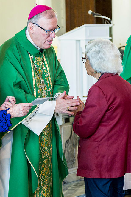 Bishop Ken Howell annoints an elderly woman