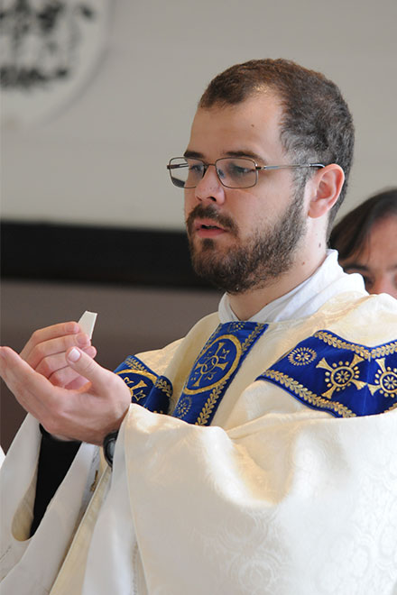 Fr Buckley holds the Eucharist