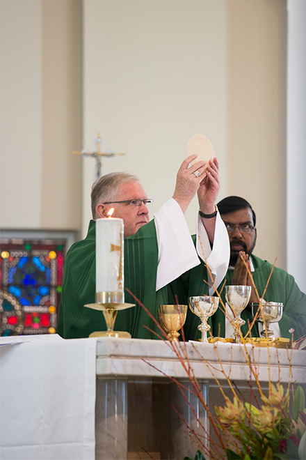 Archbishop Mark Coleridge holds the Body of Christ as he celebrates Mass at St Agatha's Church