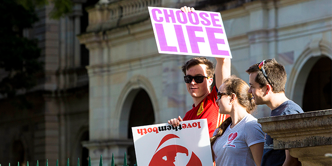 Young man holds pro-life sign in protest rally