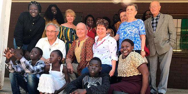 Leading with faith: FCI chaplain Scalabrinian Father Angelo Cagna with members of the Italian and Sudanese communities of Brisbane.