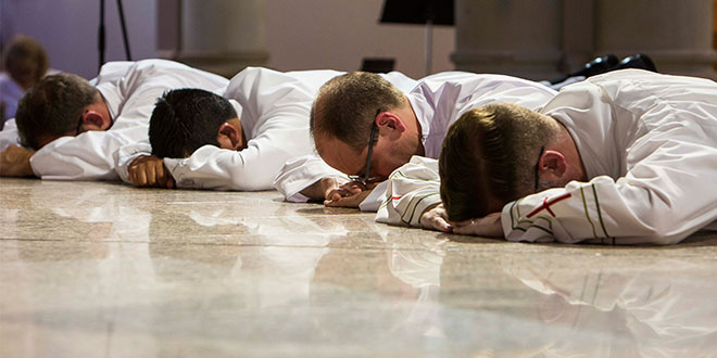 Four deacons lay prostrate on the floor of St Stephen's Cathedral
