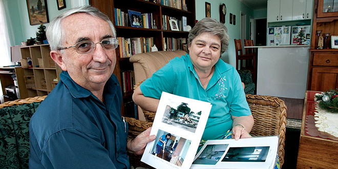 Husband and wife look through photos of the 2011 flood damage to their home