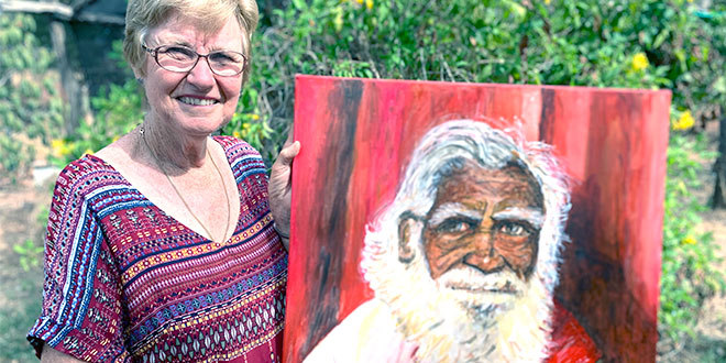 Catholic woman holds portrait of the first deacon in Australia
