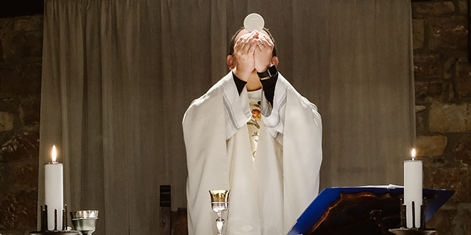 Priest during the consecration of the Mass