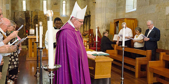 Archbishop Coleridge touches the coffin of Archbishop Bathersby