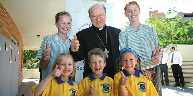 Archbishop Bathersby standing with school students