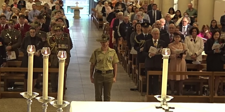 A soldier stands before the altar at St Stephen's Cathedral for the ANZAC Day Mass attended by Queensland political, judicial and defence force dignitaries.
