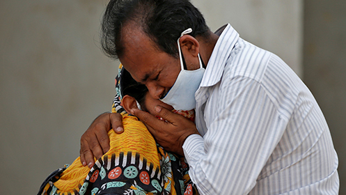 A woman is consoled by her relative outside a hospital in Ahmedabad after her husband died from COVID-19 complications.