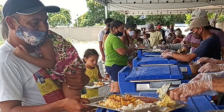 """Venezuelan refugees in Boa Vista, Brazil, receive food from """"Stirring the Pot,"""" a Catholic-run program. Catholic entities in Brazil are ramping up their efforts to feed the rising number of people going hungry, as unemployment increases and COVID-19 infections surge."""