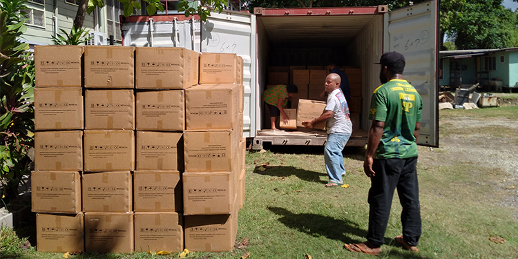 Donations: Workers move boxes filled with PPE for PNG health workers.