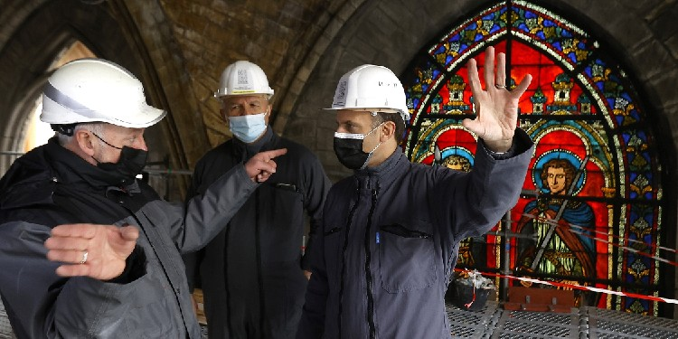 French President Emmanuel Macron, right, speaks with a worker and Gen. Jean-Louis Georgelin during a visit at the reconstruction site of the Notre Dame Cathedral in Paris April 15, 2021.