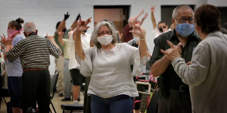 Sign language: Iris Martinez shares the sign of peace in American Sign Language during Mass at the St. Francis Borgia Deaf Center Aug. 16, 2020.