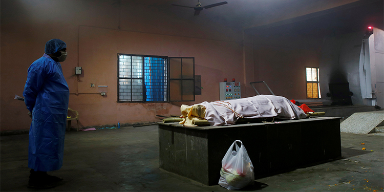 Personal grieving: A family member wearing personal protective equipment stands next to the body of a woman before her cremation at a crematorium in New Delhi. The woman died after contracting COVID-19.