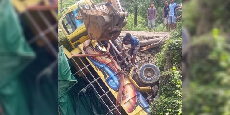 Flood toll: A truck is recovered after a section of road collapsed from torrents of water. The driver died in the accident.