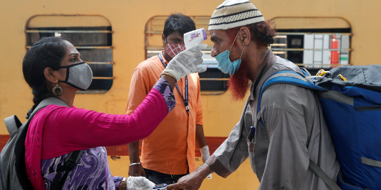 A health worker checks a passenger's temperature and pulse at a railway station platform during the coronavirus pandemic in Mumbai, India, April 7, 2021.