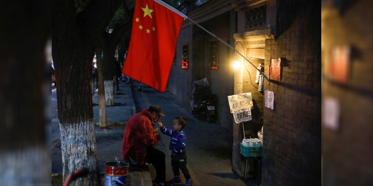 Party influence: A man and child are seen in Beijing.