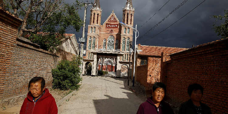Locals: Villagers are pictured in a 2018 photo walking near a Catholic church in Huangtugang, China.