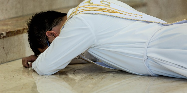 Solemn day: Fr Anh lays prostrate at his ordination.
