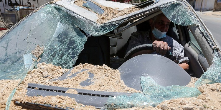 Destruction: A Palestinian man drives his car, which was damaged in an Israeli airstrike, as he heads to a garage in Gaza City May 19, 2021.