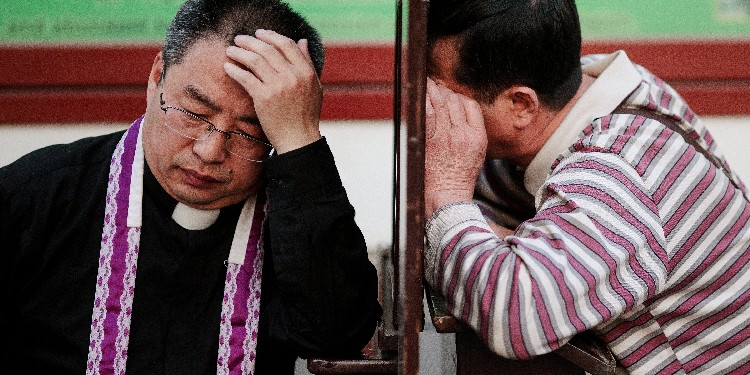 Sacraments: A priest hears confession at the Cathedral of the Immaculate Conception in Beijing.