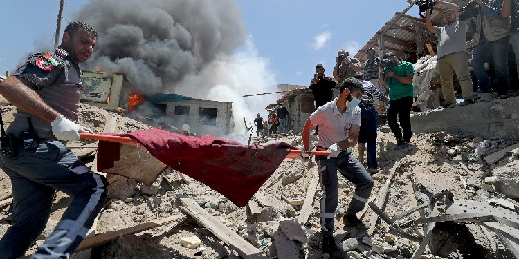 Violence: Palestinians evacuate a body from the site of Israeli strikes in Gaza City May 17, 2021.