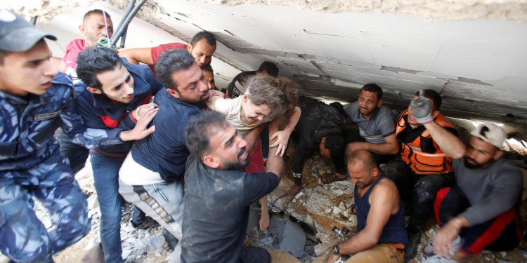 Saved: Rescuers carry Suzy Eshkuntana, 6, as they pull her from the rubble of a building at the site of Israeli airstrikes in Gaza City May 16, 2021.