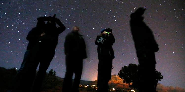 Star gazing: People use night vision goggles to look at the night sky during an Unidentified Flying Object (UFO) tour in the desert outside Sedona, Arizona. Photo CNS