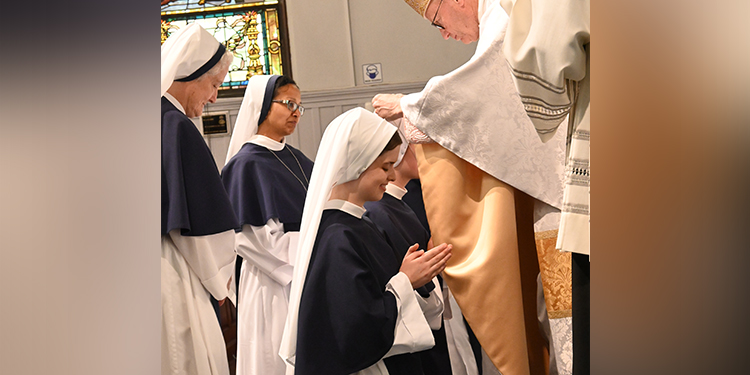 Professions: Sr Rose Patrick O'Connor receives a blessing and the Marian Medal from Bishop James Conley following her profession.