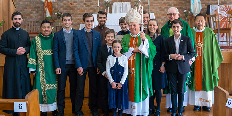 Celebration back home: Toowoomba Bishop Robert McGuckin, clergy and some of the Webb family after Mass at Sacred Heart Church Hall in Toowoomba on June 27.