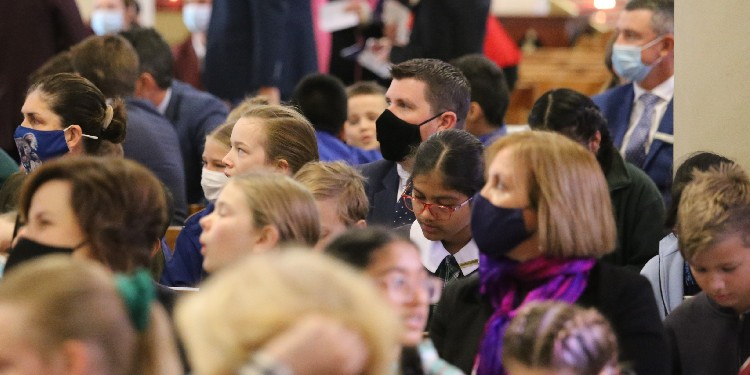 Gathering: Teachers and staff seen in masks as Catholic Education Week kicks off amid a concerning time for COVID.