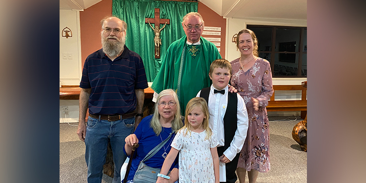Family: May with her husband Andrew (left), grandchildren Caitie and Sam Grace, daughter Mary Grace (right), and Regents Park parish priest Fr john Conway, celebrating Sam's First Communion.